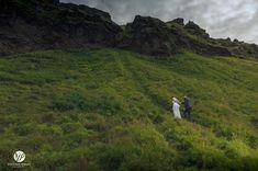 Bride and groom climbing side of mountain by Seljalandsfoss waterfall Iceland #iceland #wedding #weddingportrait #seljalandsfoss #waterfall #couple #weddingday #destinationwedding