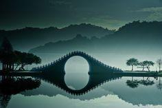 Moon Bridge in Taiwan. Moon Bridge è un ponte pedonale in legno costruito nel Dahu Park di Taipei, nel nord di Taiwan. L'acqua cristallina del Grande Lago consente un riflesso perfetto, quasi magico, ideale per una vacanza rilassante. Foto di bbe022001. Via unusualplaces.org
