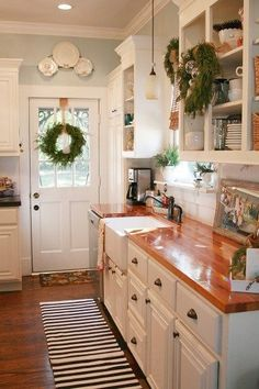 I am loving the white cabinets with the wood counter tops and pale blue paint. Very cute!