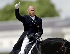 Steffen Peters of the United States waves to the crowd after riding his horse Ravel in dressage at the 2012 Summer Olympics Aug. 3.