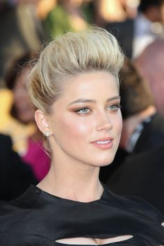 This updo is very tall and full of height up front and center with the bangs having had a tease or two (back combing) and plenty of strong hold hairspray.  The way that this front area swoops up and back like a big roll is reminiscent of how women wore their hair in the early 1900's. Her blonde color is light and bright with darker roots and undertones. The back could be brought up into a simple bun or a french braid. The event here is 18th Annual Screen Actors Guild Awards. More on Amber …