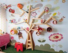 Para exibir todos os bichinhos de pelúcia da menina, o arquiteto Rodrigo Ângulo montou uma estante em forma de árvore, que completa o desenho do adesivo da parede. Os galhos são prateleiras cortadas em diferentes medidas.