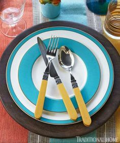 White plates rimmed in turquoise stand out against a dark charger. Vintage flatware adds a fun, retro touch to the place setting. - Traditional Home ® / Photo: Luca Trovato