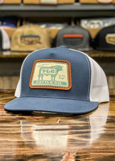 """Classic 5-panel high-profile trucker cap. """"Old-school"""" fit & finish. Logo: Embroidered Patch Material: Cotton/poly-twill front panels, Trucker mesh back Closure: Plastic snap adjustable Sizes: Adult 