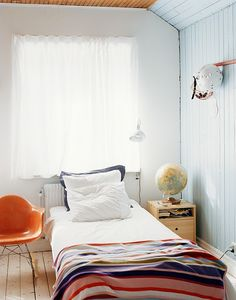 bedroom with blueish wood wall and low bed