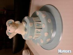 A two tier mud cake in pale blue with spots, topped with a happy elephant.