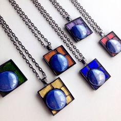 These mosaic necklaces are colorful and customizable. The pendants measure 1 inch square and hang in a 24 inch gunmetal tone chain. Each pendant includes an indigo blue iridescent glass gem. You choose the stained glass color to compliment that green gem. Available color combos are shown in the photos above. Complimentary colors available include red, green, blue, orange, yellow, purple, or dark blue. Please note that each pendant is handmade and the glass pieces are hand cut by me. This…