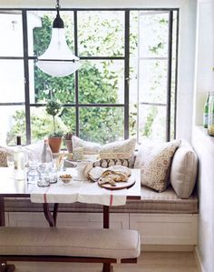 Great use of the window seat as a bench- total space saver. An antique barn table and great pillows would make this in a chef's kitchen.