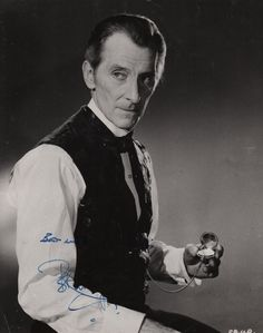 CUSHING PETER: (1913-1994) English Actor. Signed 7½ x 9 photograph of Cushing seated in a half-length pose, in costume as Baron Victor Frankenstein, holding a fob watch in one hand, from the Hammer Horror film Frankenstein Must Be Destroyed (1969). Signed by Cushing in blue fountain pen ink with his name alone to a darker area at the base of the image.