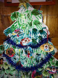 Con las manitas impresas en tinta, podemos hacer este original árbol de navidad y adornarlo con guirnaldas, fotografías,... Ellos son el centro de la Navidad y colaboran de esta forma a personalizarla.