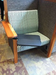 Closeup of pinwheel chair with tablet arm out. Just visible under the seat is the power outlet -- Mary Idema Pew Library