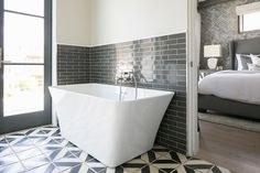 White and gray master bathroom features upper wall painted pale grey and lower wall clad in ...