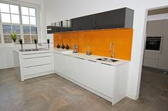 For an eye-catching modern kitchen design why not inject a bold coloured splashback for a striking contrast against your white gloss acrylic kitchen finish?   This kitchen is part of our Canary Wharf Kitchen Showroom display and in combination with black wall units this again shows off the accommodating nature of the White Acrylic kitchen.