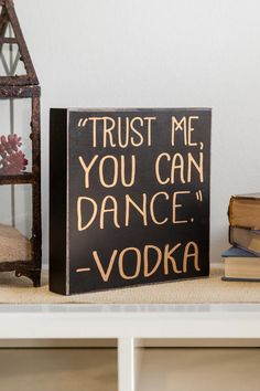 """Trust Me, You Can Dance. - Vodka<br /> <br /> With a bold look, this fun sign is perfect for setting by the bar or hanging in the kitchen! You can't go wrong buying this sign for your bestie or yourself! Pair with our additional home decor options for a complete look.<br /> <br /> - 8"""" x 8"""" x 1.5""""<br /> - Imported"""