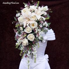 Gorgeous white, ivory, mauve, dusty lavender, and sage green, cascade bridal bouquet featuring ultra realistic, artificial lilies, roses, larkspur, zinnias, snapdragons, astilbe, and ivy. Floral Design: Something Floral / Something Spectacular (Warren, MI). Photo: Urban Fire Studio