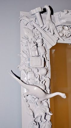 glue and spray paint trinkets onto the frame of a mirror