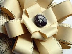 Eco-friendly bows. Upcycle an old phone book to make these beautiful bows. The White or Yellow Pages would look great on any package!  #diy #gift #bow #package #button #paper #recycle #upcycle #ecofriendly