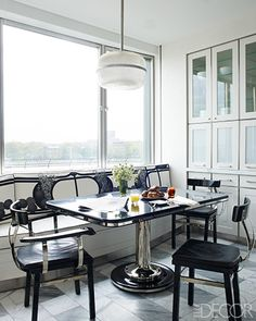 KITCHEN DINING AREA    Chairs from 1930 surround a table by Soane in the kitchen; the cabinetry, which is painted in a Benjamin Moore white, and the banquette, which is upholstered in an antique textile, are custom made.