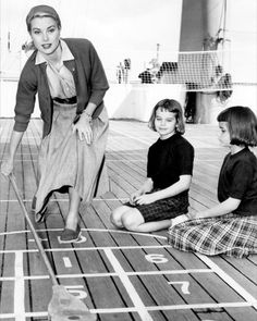 theroyalfanzine via graceandfamily:  Grace Kelly aboard the liner Constitution, on her way to Monaco to be married to Prince Rainier. She is seen here playing shuffleboard with her two twin nieces-9 year old, Margaret Ann and Mary Lee, daughters of her sister Peggy,April 11, 1956.  Margaret (known as Megan) is godmother to her cousin, Princess Caroline.