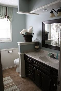Use either a half wall or a full height cabinet to divide the space between the toilet and the sink in Linda's bathroom