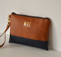 This wristlet clutch is made of cognac brown on the top and navy blue on the base, in high quality faux leather.  The interior is fully lined with cotton fabric  The letters are printed in gold-tone foil.  Fits most smartphones.  Measurements: 9 x 6  - zipper closure - inside pocket - removable wrist-strap - simple and trendy design - hand crafted  Visit my shop for more items: http://www.etsy.com/shop/navesdesign  Thanks for looking