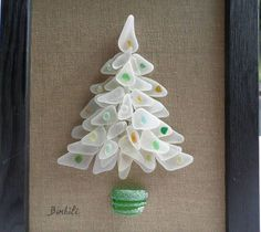 Seaglass Christmas tree, Christmas tree, white christmas decoration. White christmas tree and multicolored balls to match any interior! This Christmas tree is made of guenuine sea glass that I found on the beach at the edge of the Atlantic Ocean. It is presented in a black stained wood frame! Dimension:4.72 inches X 7.08 inches without frame 6.29 inches x 8.26 inches with the frame