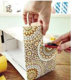 Use double-backed tape to dress up a shoe box with paper for attractive DIY storage and home decor.