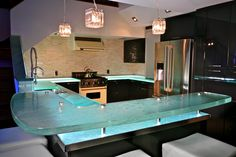 This kitchen is filled with glass.. Even if it is a small kitchen, the luminescence of the Glass Countertops makes it bigger. Perfect for the kitchen, glass will not stain and requires no maintenance.