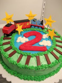 Thomas the train cake for sons 2nd birthday. Chocolate mint cake frosted with buttercream, hersheys chocolate bar rails, real Thomas train toys and the stars are construction paper