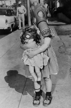 1954 photo;  The doll too, was masked when Agatha Acker, 3, joined her mother and others parading in Pasadena to urge attendance at a smog protest meeting.   © Bettmann/CORBIS