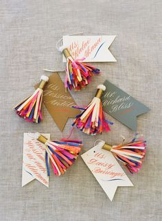 The Escort Cards: Paper tassels created by Parcel, a paper vendor whose goods are sold in Fiona's store, hung from each calligraphed place card. Photography by Liz Banfield