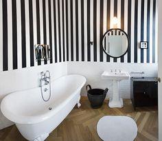 Un bagno con pareti a righe bianche e nere