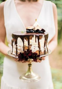 SERIOUSLY, how DELICIOUS does this semi naked chocolate drip cake look?! Perfect for outdoor, rustic, boho weddings and if you're having a wedding outdoors, this relaxed but oh-so decadent style will please all your guests! See more of this Rustic Riches: Boho Woodland Wedding Styled Shoot on Wedding Ideas