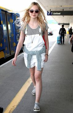 Elle Fanning at LAX in a striped shirt, a backpack, and the cutest overalls ever.