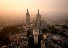 The Sacré-Cœur in Paris awash in a golden glow peeks through a hazy sunrise.