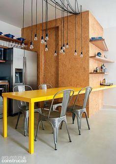 Cozinha com parede revestida com OSB, mesa de jantar em laca amarela, iluminação pendente estilo industrial.