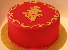 """""""This 60th birthday cake is covered in lucky red and topped with a handcarved chinese symbol for longevity painted in edible gold"""""""