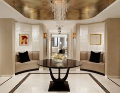 Design Ideas: Beautiful Taupe Foyer With Round Glass Table. shiny round table. crystal chandelier. taupe sofa. modern foyer. black sofa cushions.