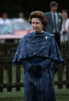 Caped and ready at the Guards polo club, Windsor, in 1984, Queen Elizabeth softens the blue ensemble with ruffle detailing and a statement brooch.