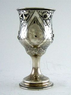"An American Coin silver goblet, maker's mark of charters, Cann & Dunn, New York, Circa 1850. Of bell-shaped form on a circular foot chased with blossoms against a stippled ground, enclosing a cartouche on either side, one side engraved presented/to/Capt. Elias D. Knight/as a/token of gratitude & esteem/by/James L.L. F. Warren; Height is 8 1/4"" inches, Weight is 9.05 Troy ounces"