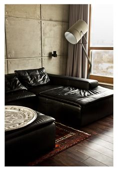¡Este rincón de lectura es una pasada! La pared de cemento con los altavoces empotrados, esa lámpara que enfatiza el aire industrial de la estancia y el maravilloso sofá negro con chaise-longue.