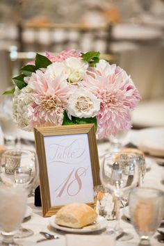 Pink and gold table number + centerpiece idea - white + pink table number in gold metallic frame displayed with light pink dahlias {Jessica Hill Photography}