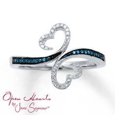 From the Open Hearts Waves by Jane Seymour collection, resplendent waves of round blue diamonds embrace the classic Open Heart design, which is embellished with round white diamonds. The ring for her is fashioned in sterling silver with 1/10 carat total weight of diamonds. Blue diamonds are treated to permanently create the intense blue color.