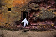 A woman enters an ancient medieval church that is carved into solid rock in Lalibela, Ethiopia. Lalibela is famous for their monolithic rock-cut churches. The churches themselves date from the seventh to thirteenth centuries, and were declared a UNESCO World Heritage Site in 1978. Steve McCurry.