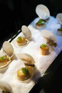 Scallops topped with sea grapes are served in their shells and placed on ice.: