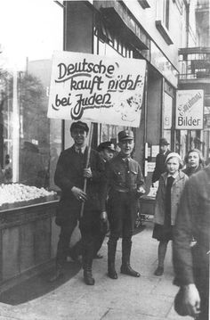 "Germany, An SA soldier near a Jewish owned store on the day of the boycott.  The sign reads: ""Germans! Do not buy from the Jews."""