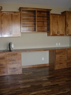 LDK Home office with wood flooring, built-in desk and upper cabinets.