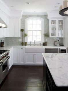 L shaped kitchen with island. Cabinets, glass doors, farmers sink, tile to the ceiling, beautiful granite. And the cherry on top, a wolf range