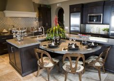 This subtly bespoke kitchen features a standout L-shaped island in dark stained wood, with a soft grey marble countertop. There's a large curved dining table built into the center of the frame, with room for a trio of seats. With a built-in sink and abundant storage, this is an exceptionally useful island design.