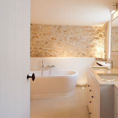 Clean contemporary bathroom furnishings against a aged stone wall.